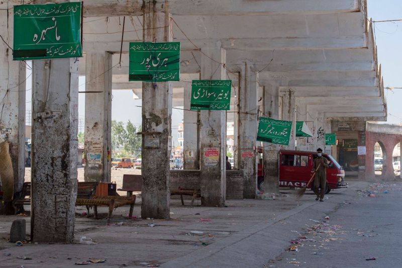 A sweeper cleans a deserted bus station after the provincial government suspended public transport during a lockdown in Peshawar, Pakistan, on April 3.