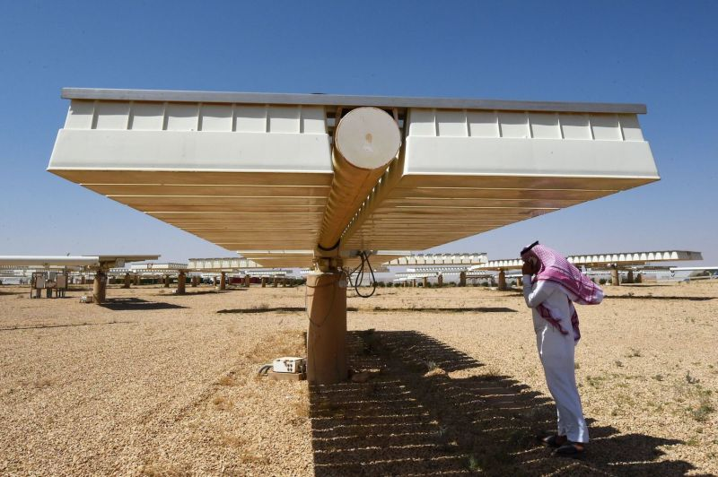 A Saudi man talks on his cell phone under the shade of solar panel at a solar plant in al-Uyayna, north of Riyadh, on March 29, 2018.