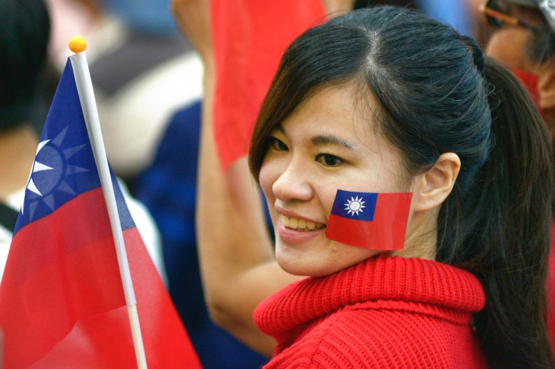 A woman holds Taiwanese flag during local elections in Taipei on Nov. 24, 2018.