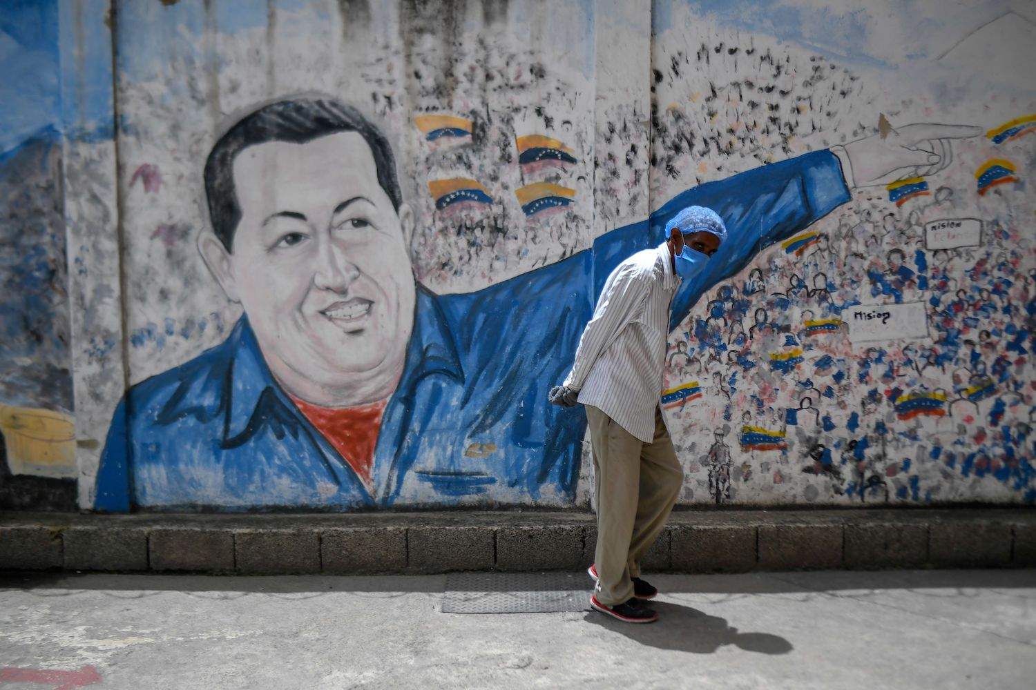 A man wearing a protective mask walks past a mural depicting former President Hugo Chavez at the Perez de Leon Hospital in eastern Caracas on June 23, 2020.