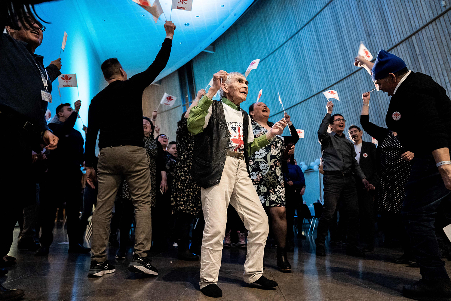 Members of the Siumut party wave flags as they celebrate exit poll results during the legislative election in Nuuk, Greenland, on April 6. EMIL HELMS/Ritzau Scanpix/AFP via Getty Images