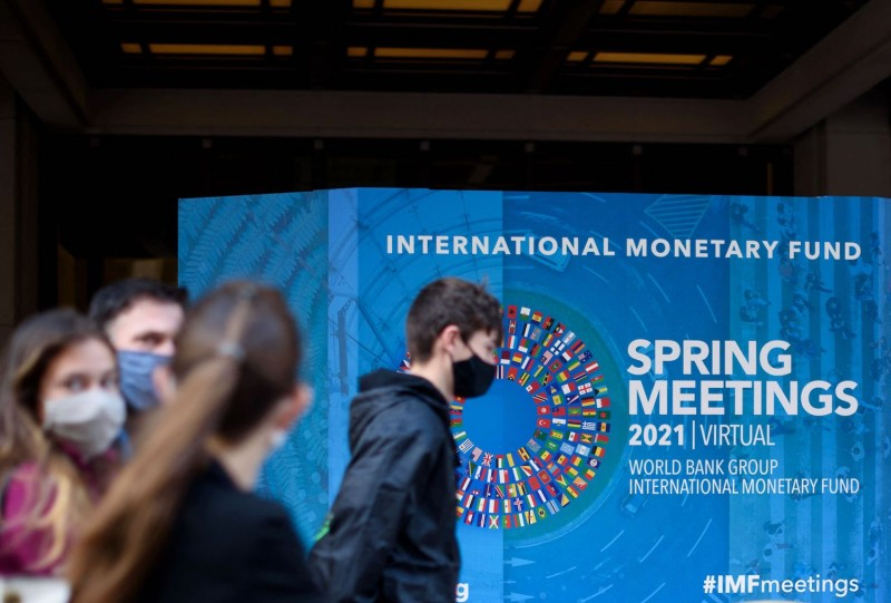 People walk past an International Monetary Fund headquarters building.