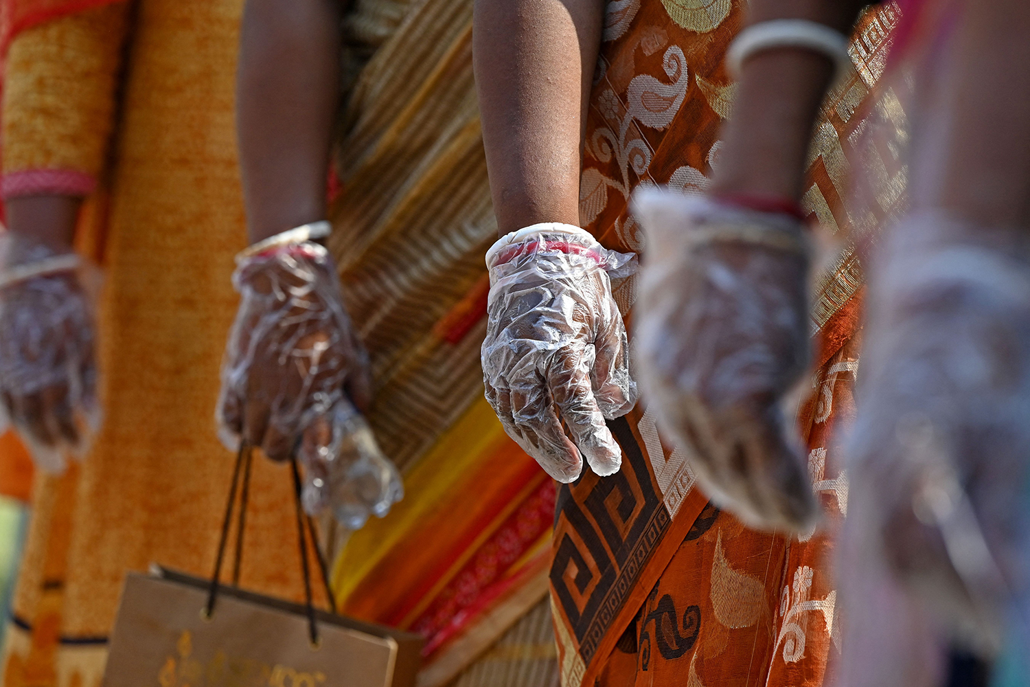 Following COVID protocols, voters wear gloves as they stand in line at a polling station to cast ballots during elections in Kolkata, India, on April 17. DIBYANGSHU SARKAR/AFP via Getty Images