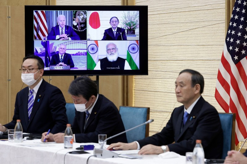 Japan's Prime Minister Yoshihide Suga (right) sits next to a monitor displaying a virtual Quadrilateral Security Dialogue meeting with U.S. President Joe Biden (top left), Australia's Prime Minister Scott Morrison (bottom left), and India's Prime Minister Narendra Modi (bottom right), in Tokyo on March 12.
