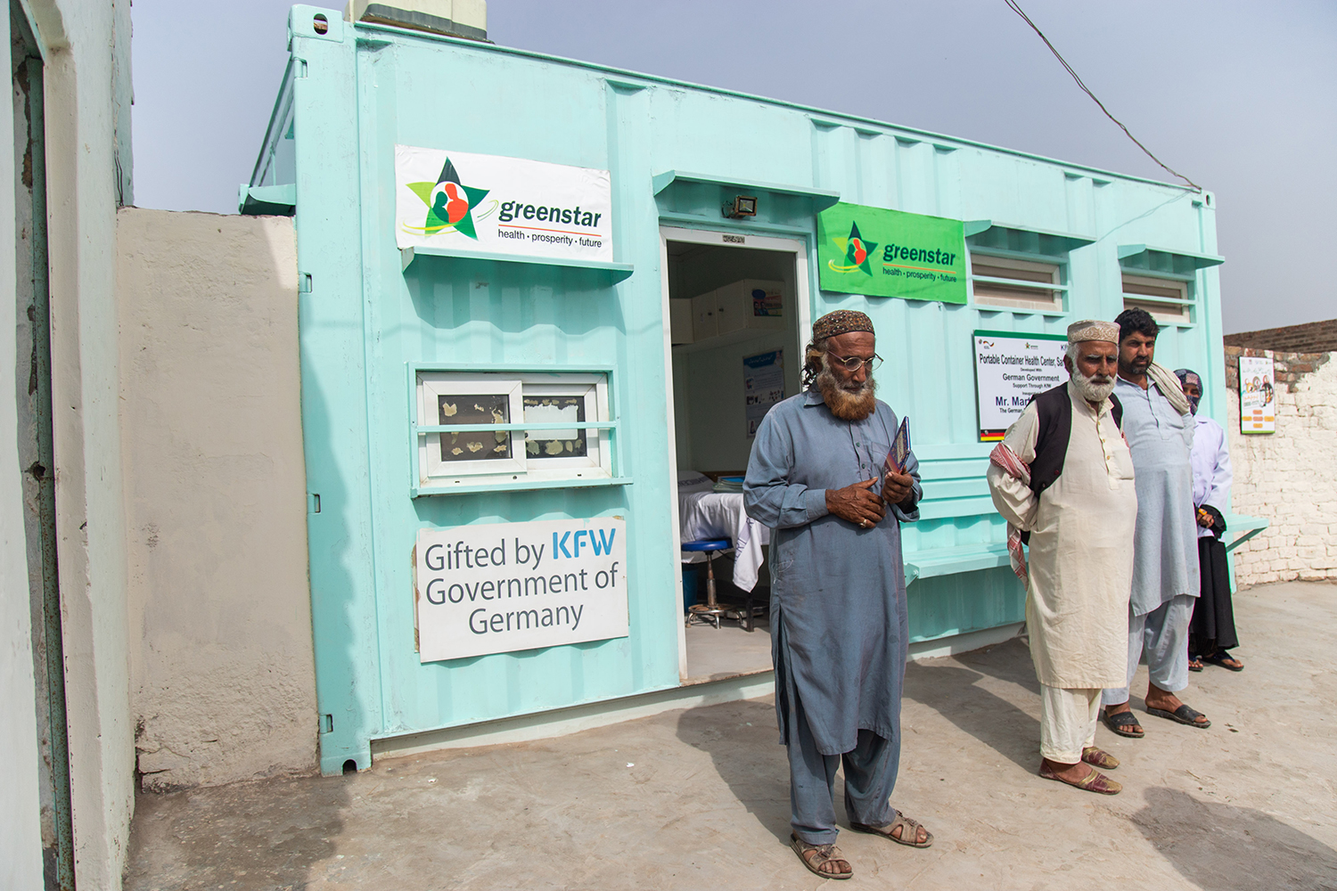 Men stand at a container clinic that provides women health services in a village outside Sargodha, Pakistan.