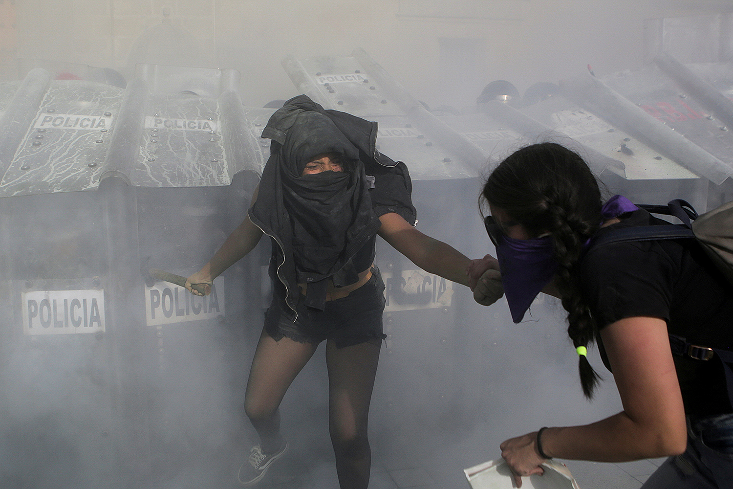 Women clash with police officers behind riot shields during a protest in support of Victoria Salazar, a Salvadoran woman who died after a Mexican police officer was seen in a video kneeling on her back, in Mexico City on April 2. Raquel Cunha/Reuters