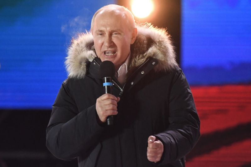 Putin clenches his fist while addressing a crowd