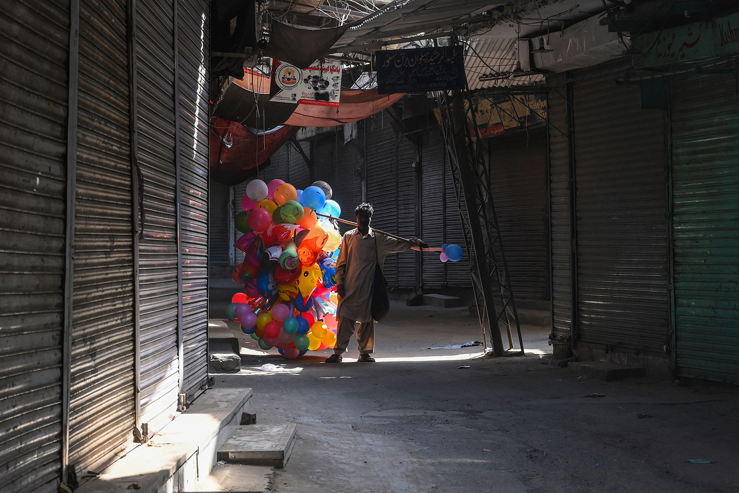 A balloon vendor walks past a shuttered market in Lahore, Pakistan, on April 11 as a lockdown was imposed to control the spread of the coronavirus. ARIF ALI/AFP via Getty Images