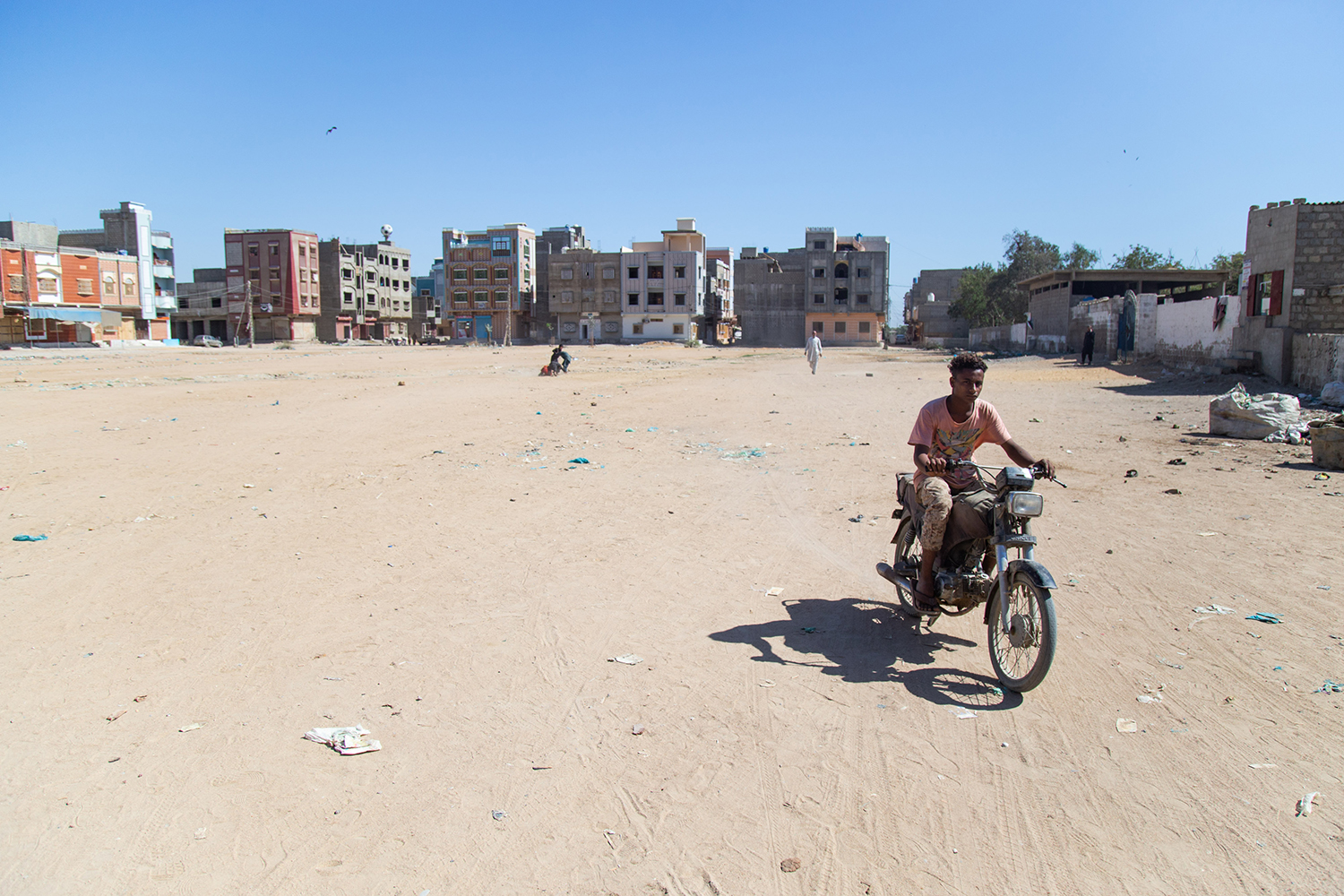 A boy rides a motorcycle through an empty dirt log near a midwife's clinic in Karachi.