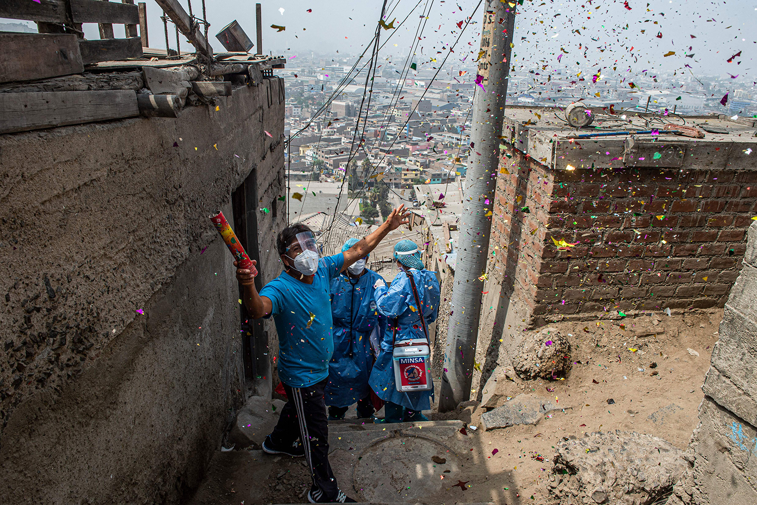 A man celebrates after health workers inoculate a woman with a dose of the Pfizer-BioNTech vaccine at her house in Lima, Peru, on April 28. ERNESTO BENAVIDES/AFP via Getty Images
