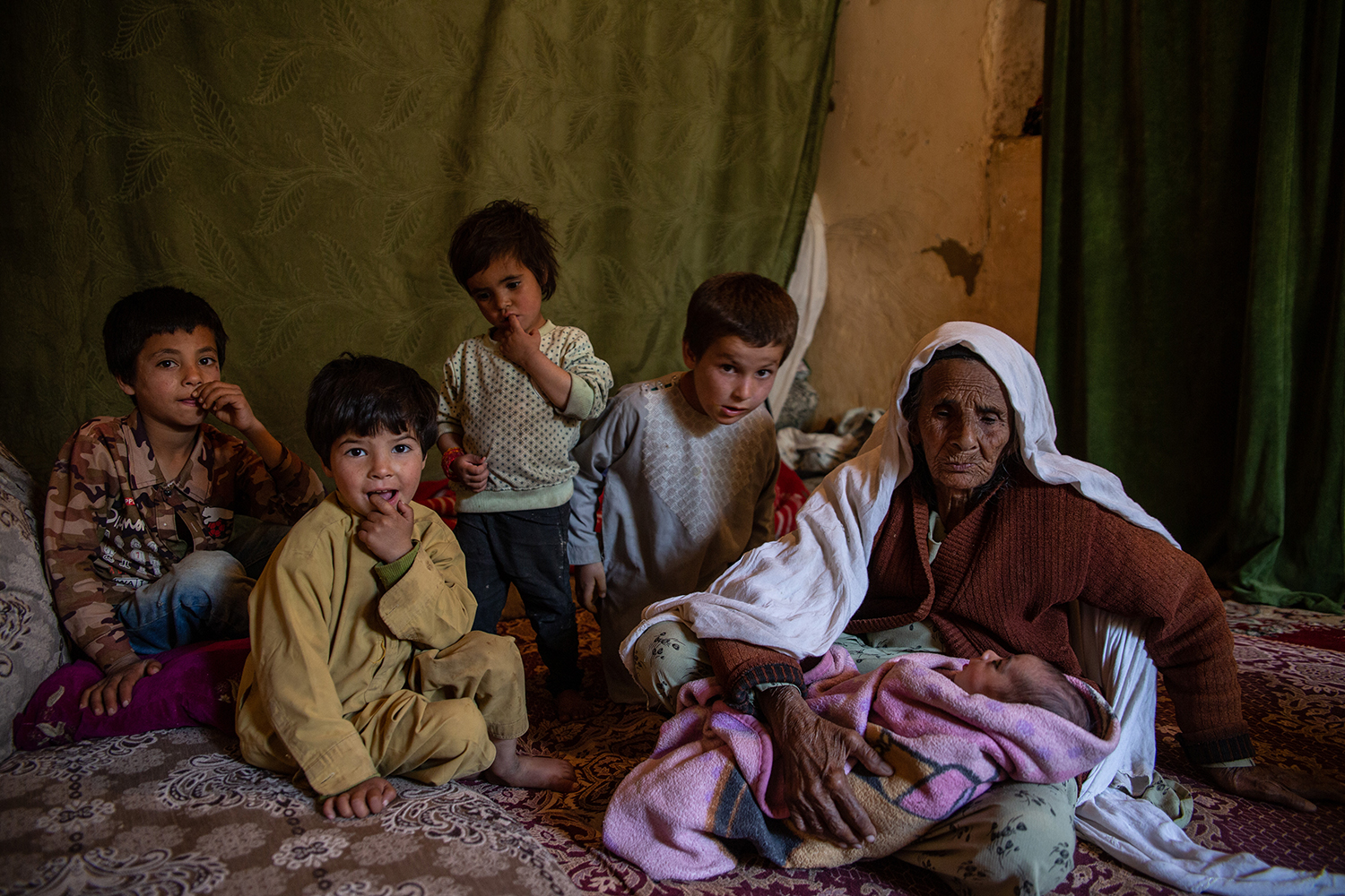 An Afghan woman surrounded by children in her house in Qarabagh.
