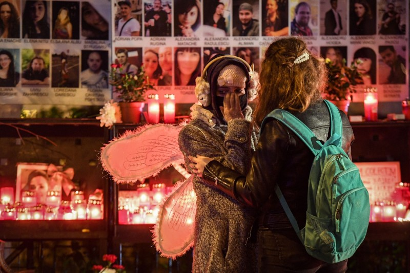 """A young girl wearing wings is embraced by another next to candles lit in the memory of the victims of  the """"Colectiv"""" nightclub fire in Bucharest, Romania on October 30, 2020."""