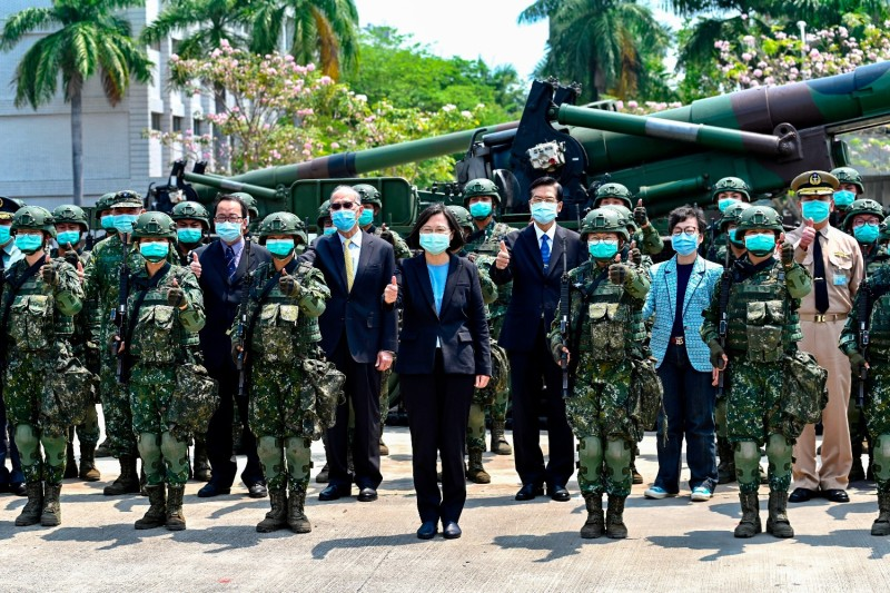 Tsai Ing-wen stands in front of a group of masked soldiers.