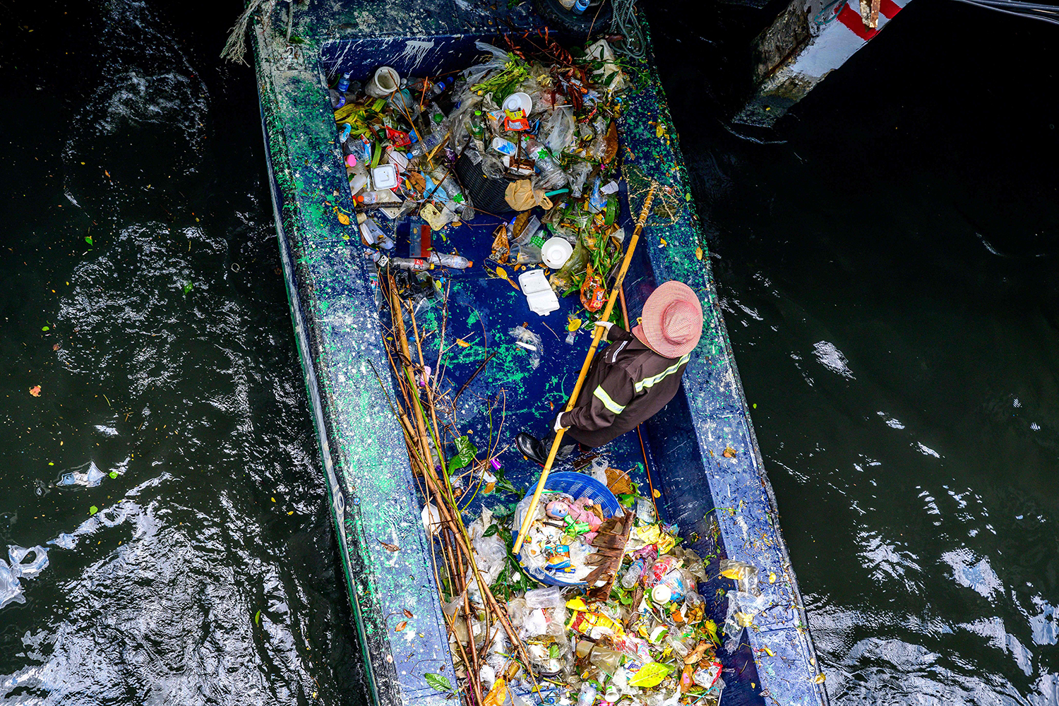 A municipal worker uses a net to pick out garbage from a canal in Bangkok on April 16. MLADEN ANTONOV/AFP via Getty Images