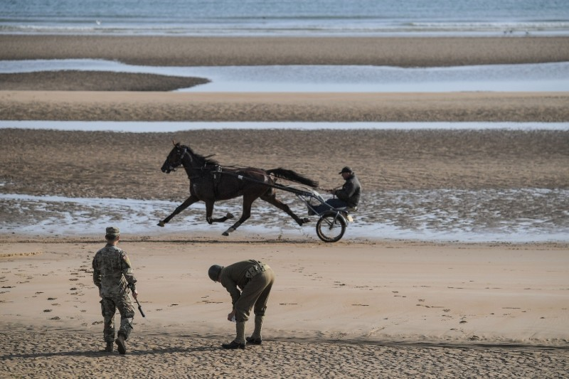 A U.S. soldier dressed in a World War II military uniform picks up sand from Omaha beach next to a U.S. soldier looking at a man driving a horse sulky on the sidelines of a ceremony in Saint-Laurent-sur-Mer, western France, on June 5, 2019.