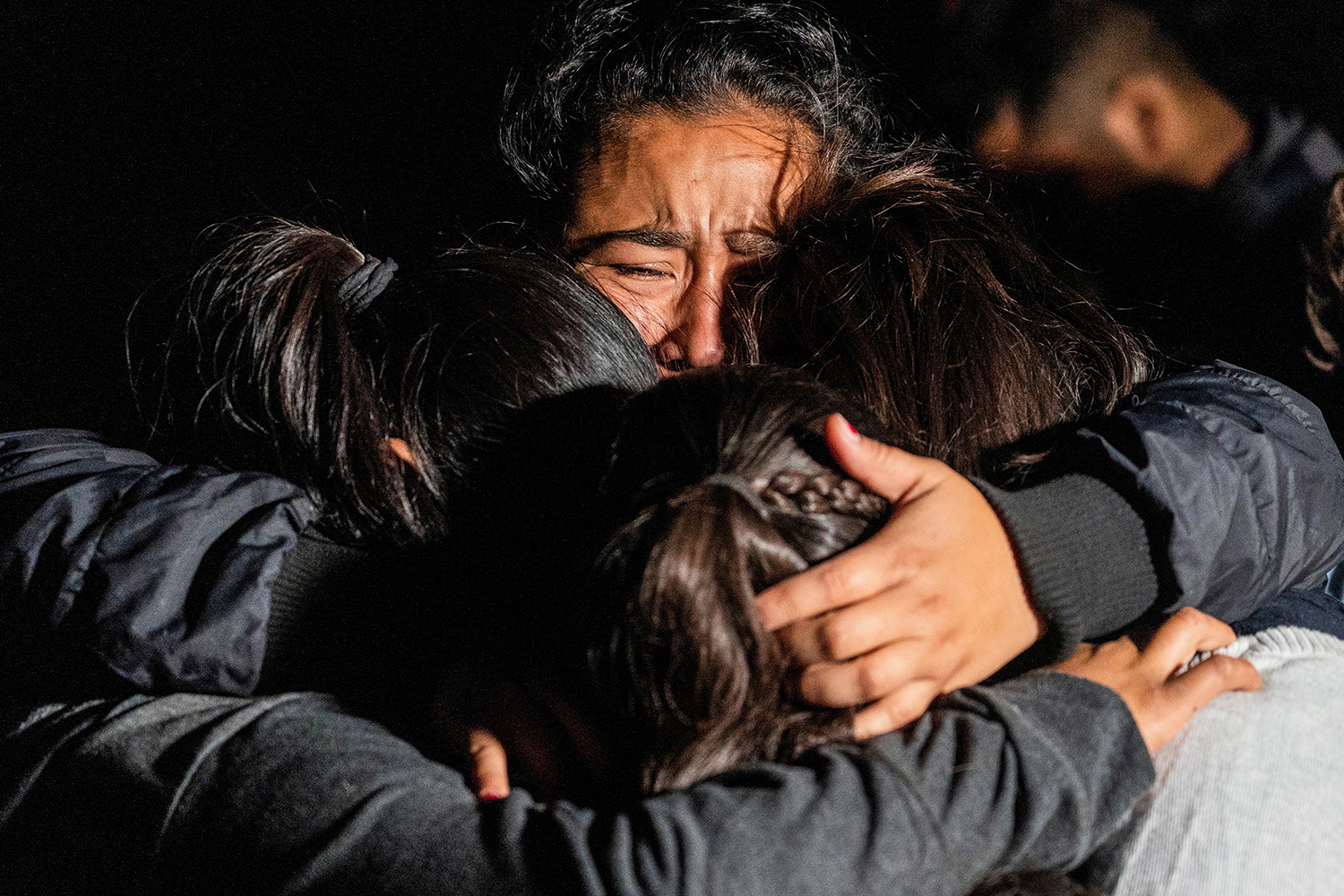 Asylum-seeking migrant families from Guatemala embrace after crossing the Rio Grande into Roma, Texas, from Mexico on April 20. Go Nakamura/Reuters