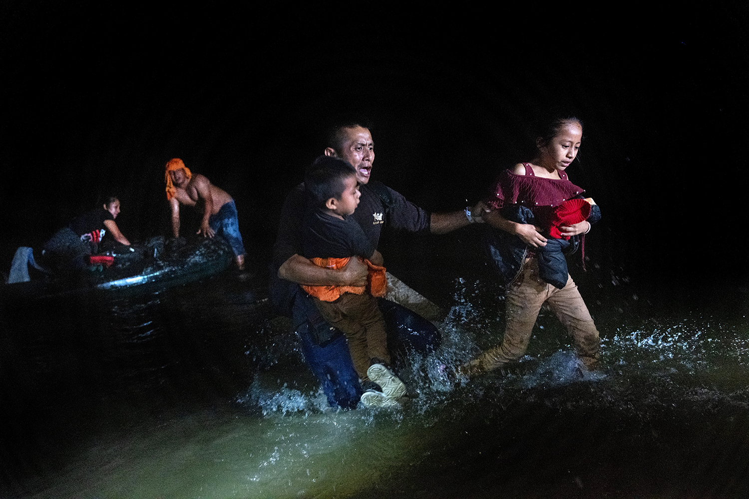 A migrant father grips his children while walking ashore on the bank of the Rio Grande at the U.S.-Mexico border in Roma, Texas, on April 14. John Moore/Getty Images