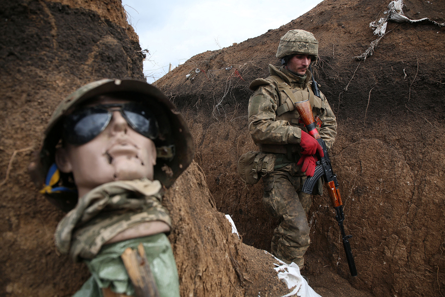 A Ukrainian serviceman walks in a trench near a mannequin as he works his post on the front line with Russia-backed separatists near the town of Zolote, Ukraine, on April 8. STR/AFP via Getty Images