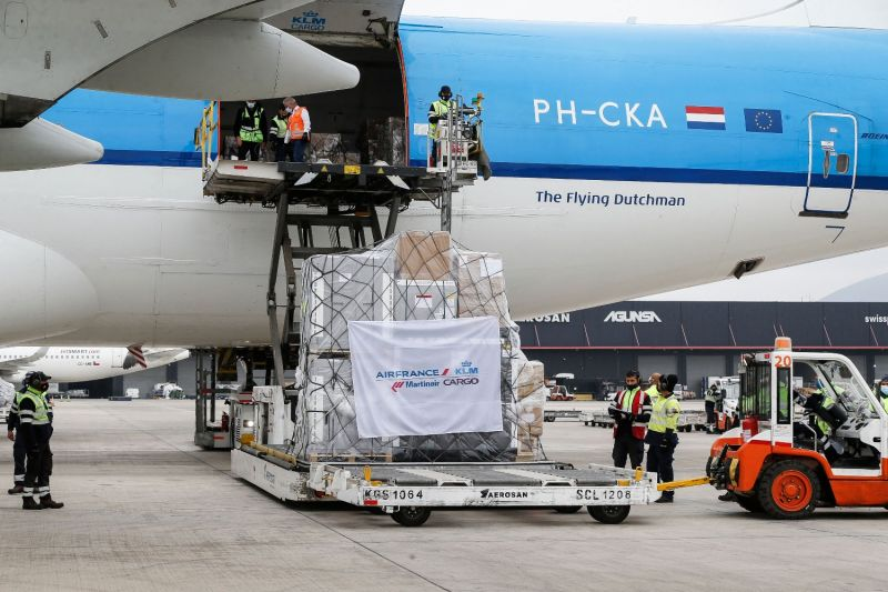 Workers unload vaccines from an airplane.