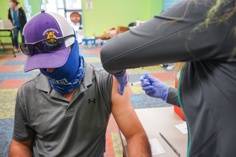 A health care worker vaccinates a man.