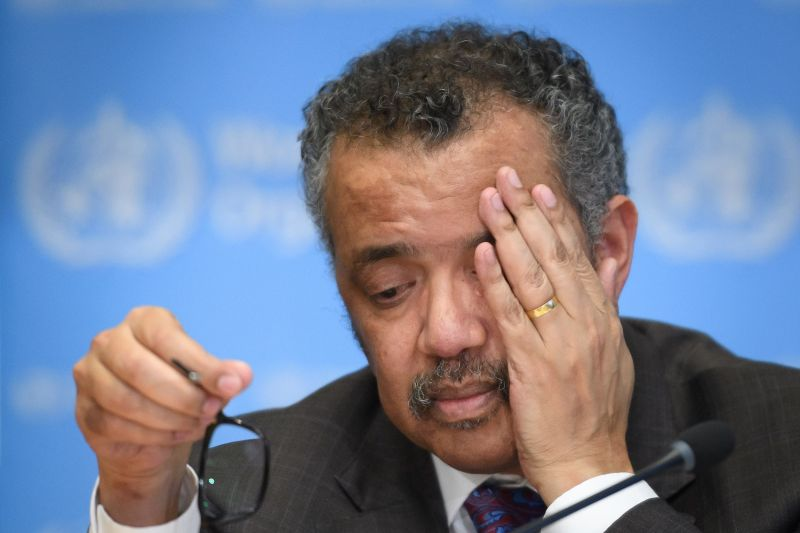 WHO Director-General Tedros Adhanom Ghebreyesus takes off his glasses and rubs his eyes.