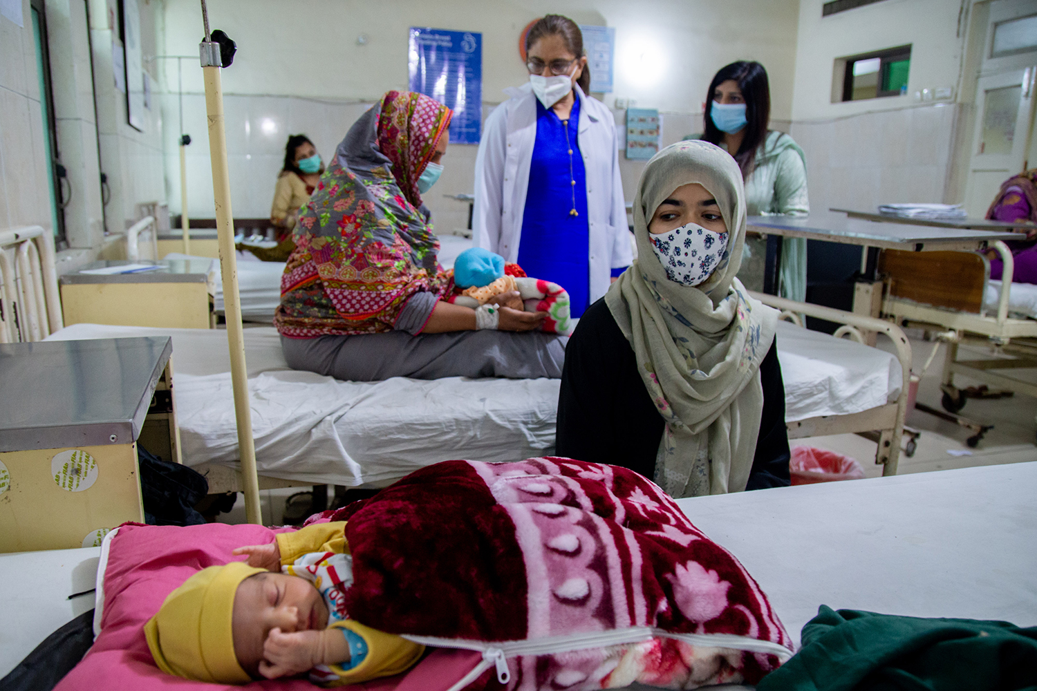 A woman sites with her baby at a health center in Lahore.