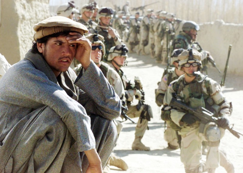 An Afghan man squats while a group of U.S. Army soldiers from the 82nd Airborne Division secure the local bazaar in Yayeh Kehl, near Kabul, Afghanistan, on Nov. 14, 2002.