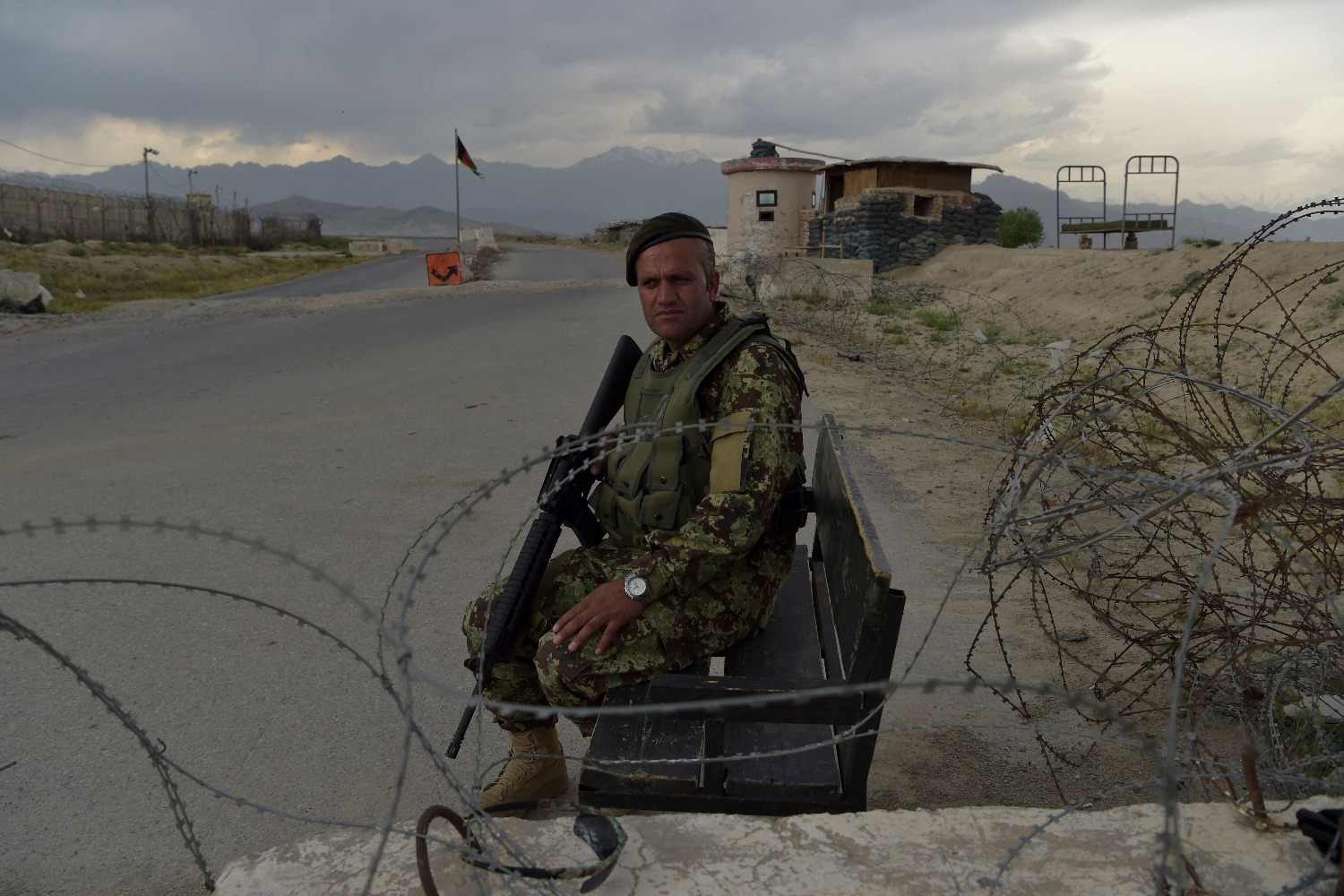 An Afghan soldier sits at a road checkpoint near a U.S. military base.