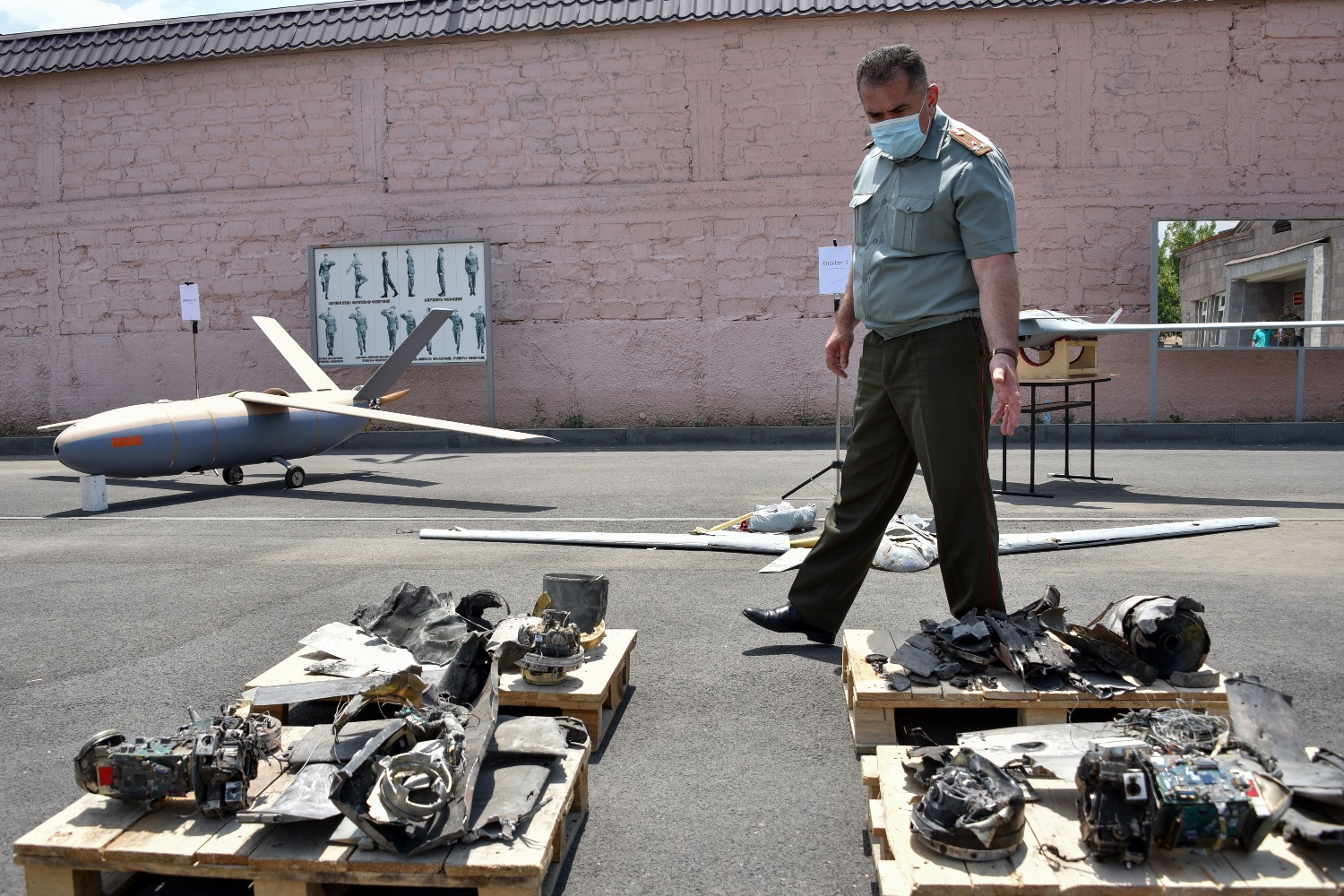 An official walks among objects that Armenia presented as captured and downed Azerbaijani drones.