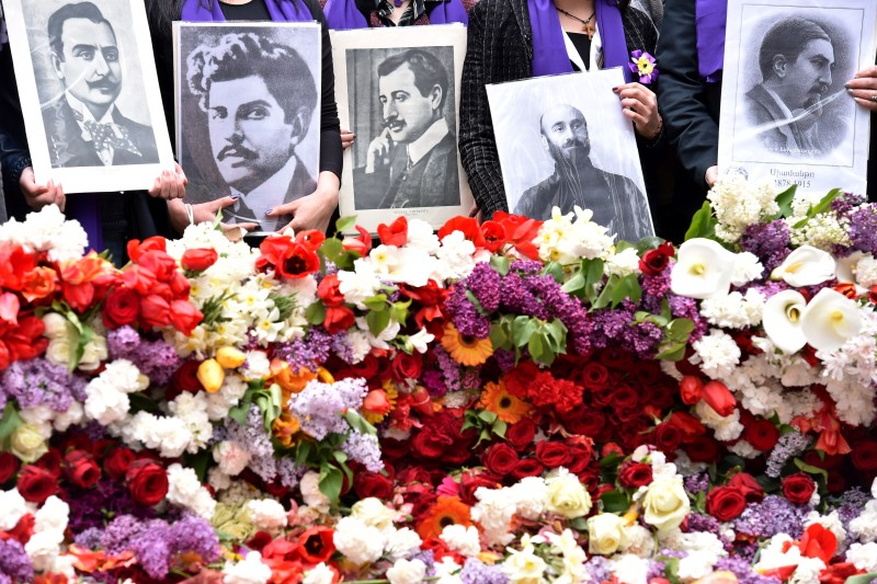 People hold photographs of Armenian writers and artists who were among the Armenian intellectuals arrested for deportation by Ottoman forces in 1915 at the Tsitsernakaberd Memorial in Yerevan, Armenia, on April 24, 2015.
