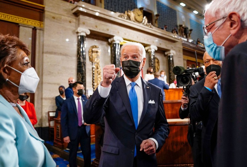 U.S. President Joe Biden gestures as Representative Maxine Waters (D-CA) and Senator Bernie Sanders (I-VT) look on after he addressed a joint session of Congress at the U.S. Capitol in Washington, DC, on April 28, 2021.