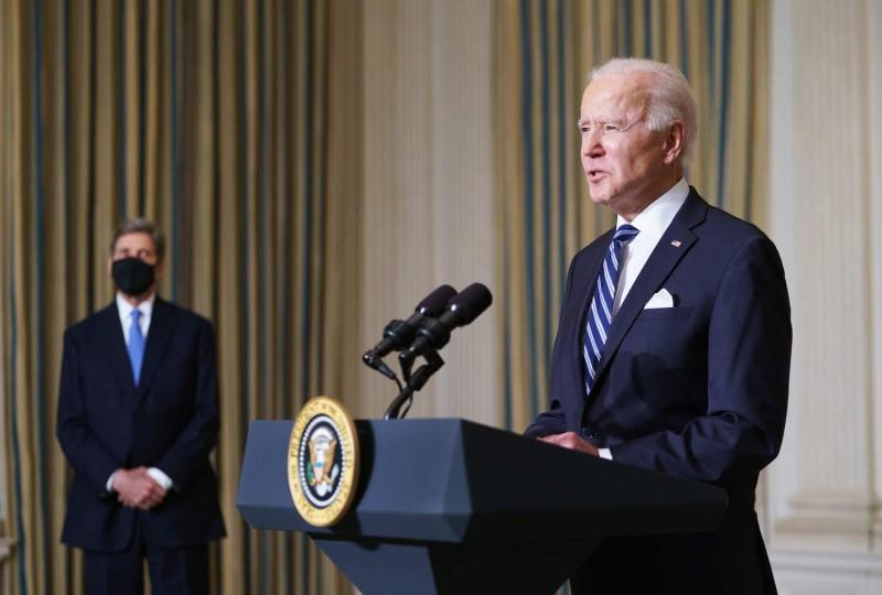 U.S. climate envoy John Kerry listens to President Joe Biden speak on tackling climate change at the White House in Washington on Jan. 27.