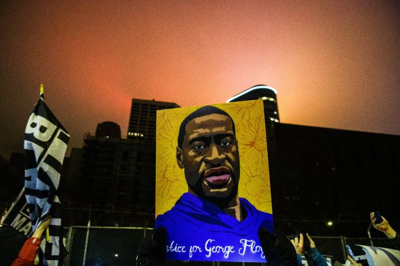 A demonstrator holds up a portrait of George Floyd.