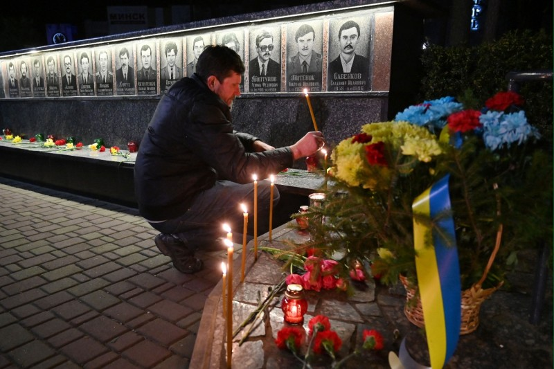 A man lights a candle at a monument to Chernobyl victims.