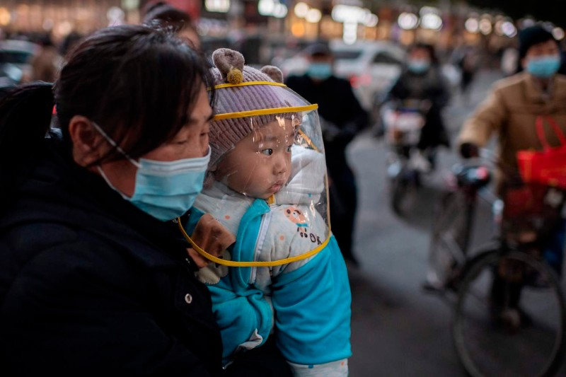 A woman holds a baby wearing a protective shield during rush hour in Wuhan, China, on Jan. 13.