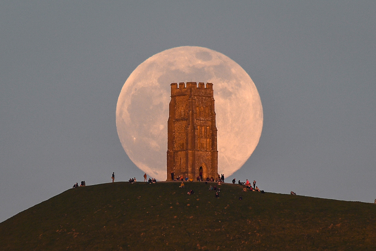 The pink supermoon rises behind Glastonbury Tor in England on April 26. Finnbarr Webster/Getty Images