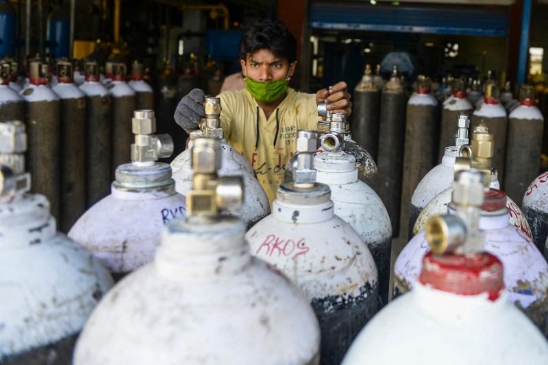 A worker arranges transport of medical oxygen cylinders.