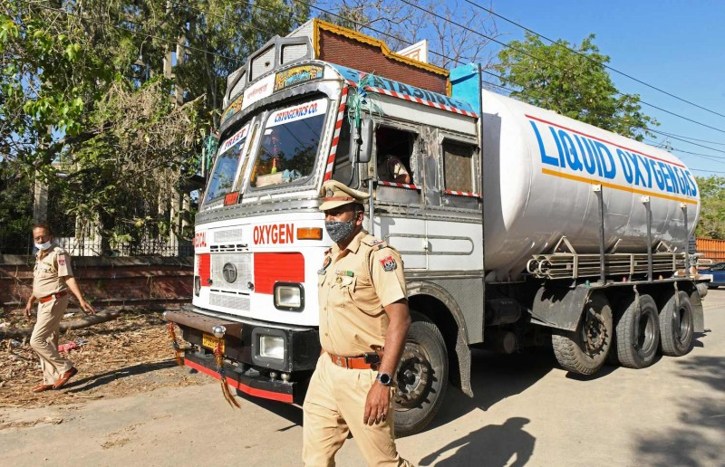 Police personnel escort a truck carrying medical liquid oxygen in India.