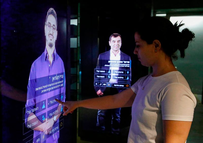 A visitor touches an interactive display showing a projection of Aziz Kaddan, an Israeli Arab entrepreneur and the CEO of Myndlift, at the Peres Center for Peace and Innovation in Tel Aviv, Israel, on Sept. 3, 2019.