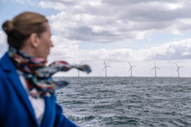 Danish Prime Minister Mette Frederiksen stands on a boat looking toward wind turbines in the Middelgrunden offshore wind farm in Oeresund, between Denmark and Sweden, on April 22.