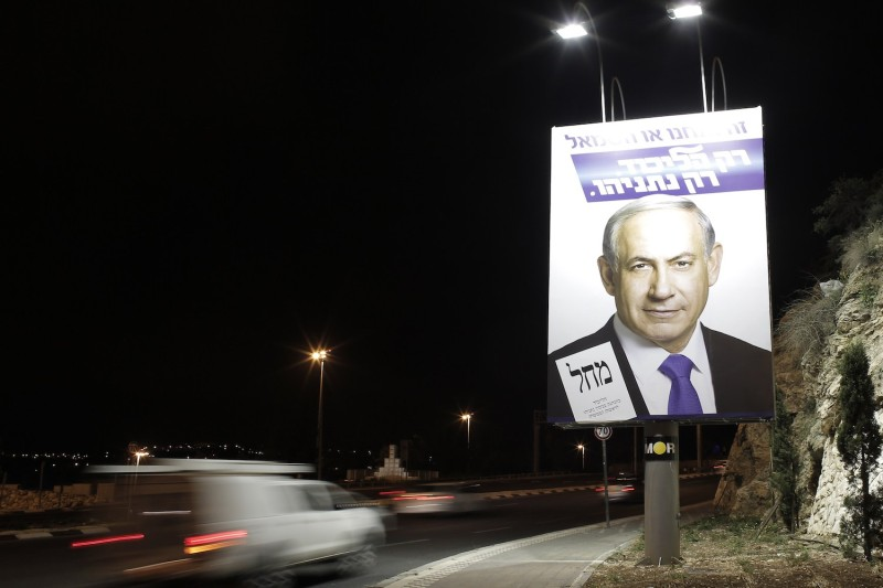 A car drives past a campaign billboard of Israeli Prime Minister Benjamin Netanyahu.