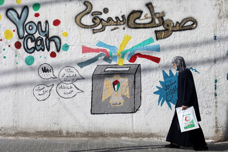 Palestinian woman walks past election mural in Gaza.