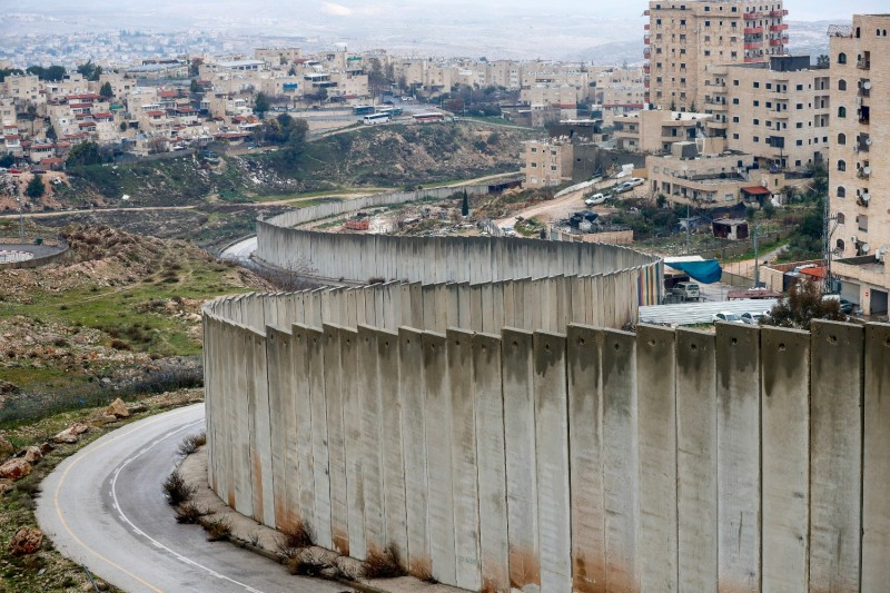 Israel's controversial separation wall runs between the Israeli settlement of Pisgat Zeev (left), built in a suburb of East Jerusalem, and the Palestinian Shuafat refugee camp (right) on Feb. 11.