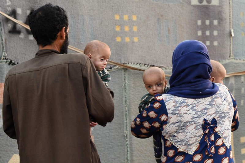 A man and woman carry malnourished children at a camp for Syrians displaced by conflict.