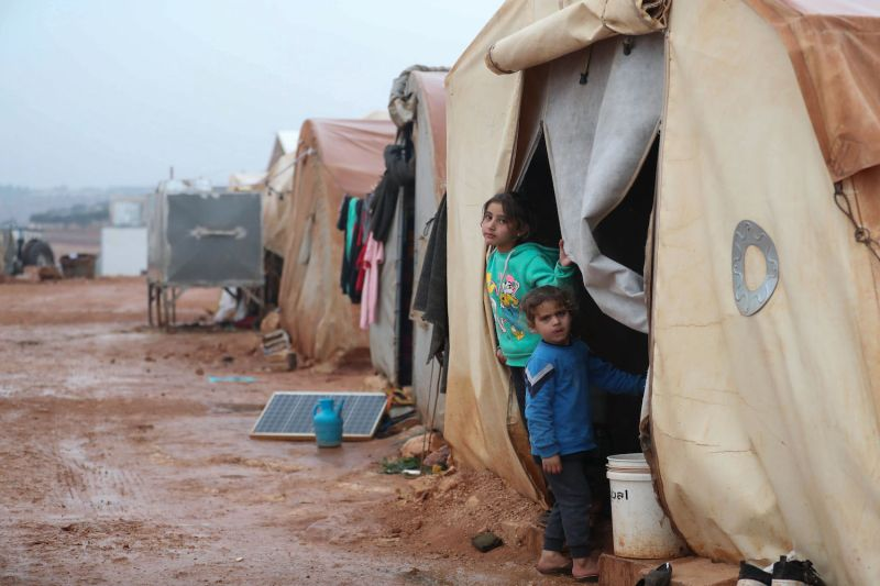 Two girls stand at the entrance of a tent in an IDP camp in Syria.
