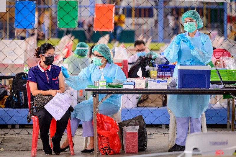 A health worker administers the vaccine developed by China's Sinovac firm to a woman at Saeng Thip sports ground in Bangkok on April 7.
