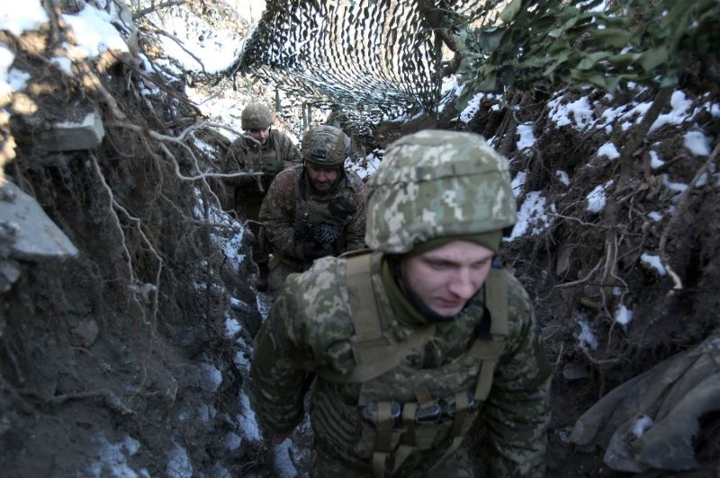Ukrainian servicemen stand in position on the front line.
