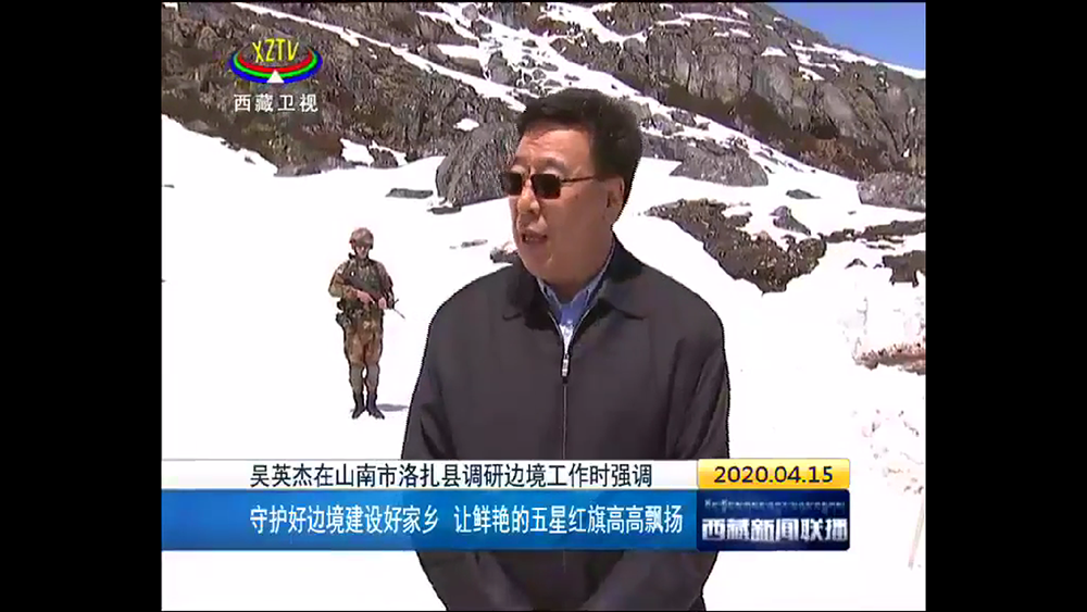 An armed PLA soldier stands guard behind Wu, the TAR party secretary, during his visit to the military outpost on the Ngarab La pass