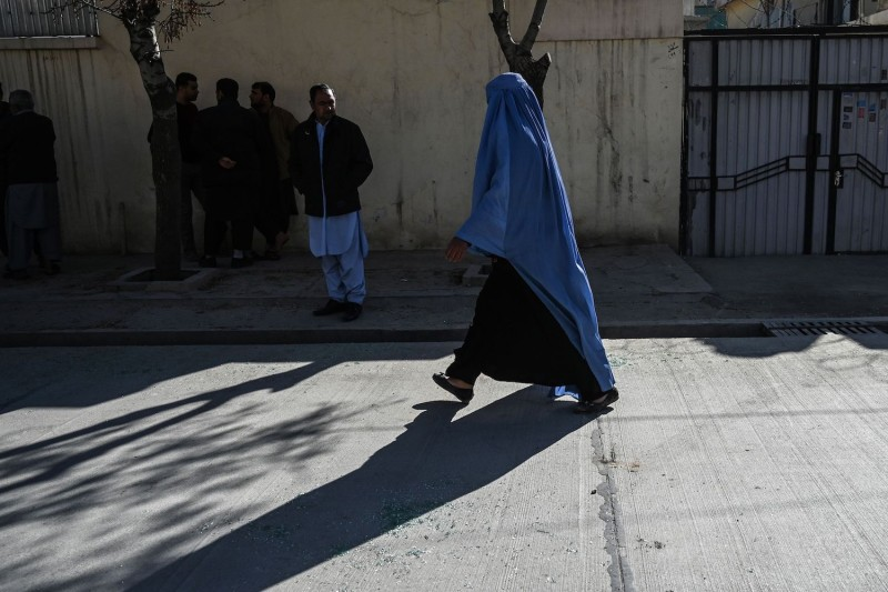 A woman wearing a burqa walks past the site of a shooting in Kabul.