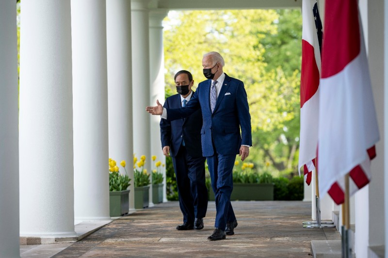 U.S. President Joe Biden and Japanese Prime Minister Yoshihide Suga walk along the Rose Garden Colonnade as they arrive for a news conference at the White House in Washington on April 16.